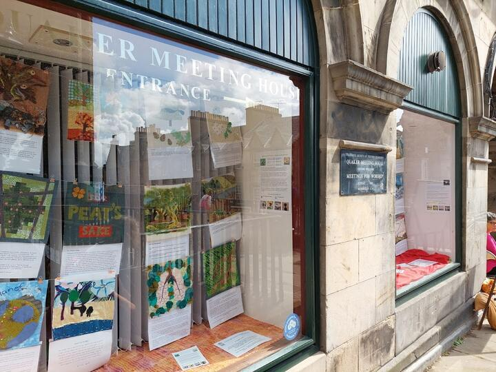 Quaker Meeting House window with sewn banners and explanations about the panels in the windows.