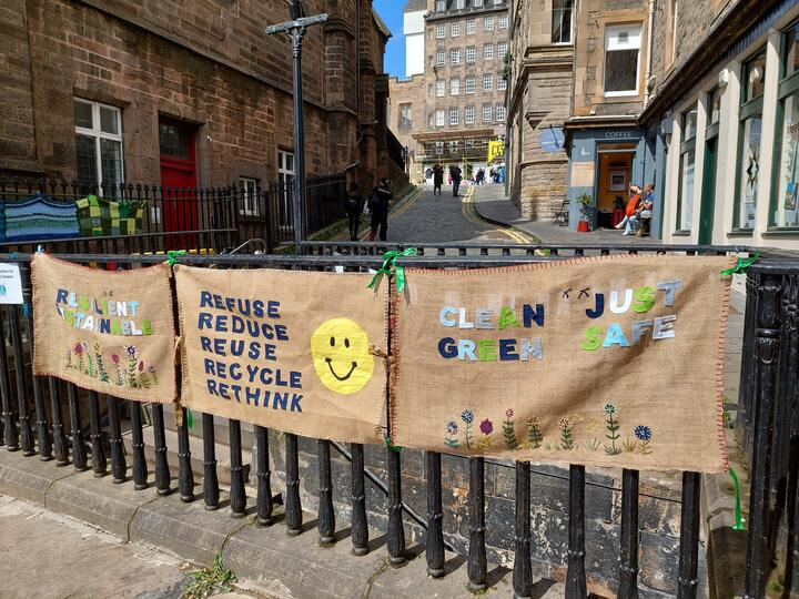 """Three banners tied to a railing on an Edinburgh Street. They are hessian with words appliqued on. Left it says """"Resilient, Sustainable"""", middle """"Refuse, Reduce, Reuse, Recycle, Rethink"""", right """"Clean, Just, Green, Safe"""""""