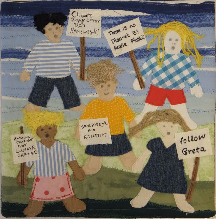 """Appliqued panel of 5 children holding placards. These say """"There's no Plan-et B"""" """"Climate Change is Worse Than Homework"""" """"Follow Greta"""" """"Human Change Not Climate Change"""" and """"School Strike for Climate"""" in Swedish."""