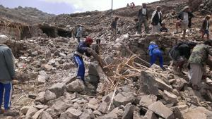 Villagers scour rubble for belongings scattered during the bombing of Hajar Aukaish - Yemen - in April 2015